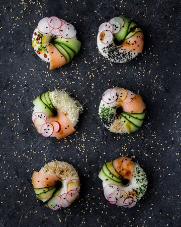Sushi donuts with salmon, cucumber and radish on dark background top view. Hybrid Foods.