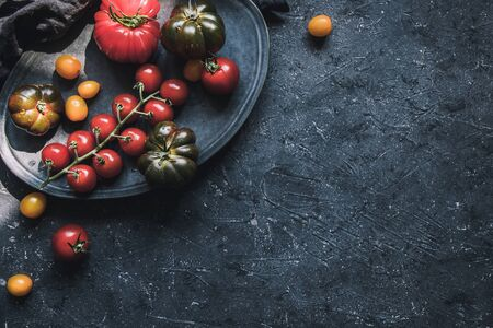 Ripe colorful different tomatoes on plate, top view. Food background with copy space.