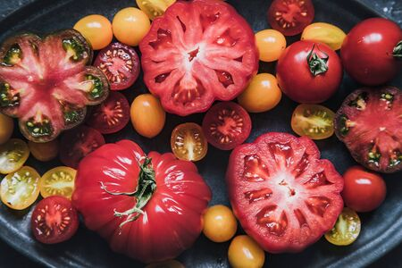 Colourful juicy food background. Fresh juicy tomatoes on plate