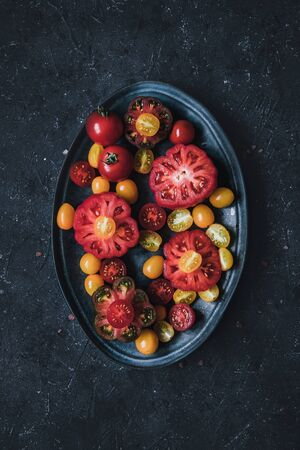 Colourful whole and halved tomatoes on plate. Beautiful juicy vegetables.