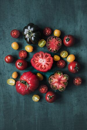 Colorful beautiful juicy tomatoes on green table, top view 스톡 콘텐츠