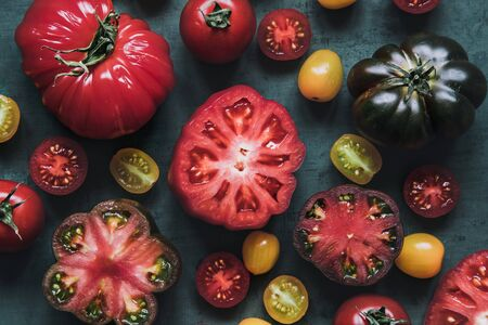 Colourful juicy food background. Fresh juicy tomatoes on green background