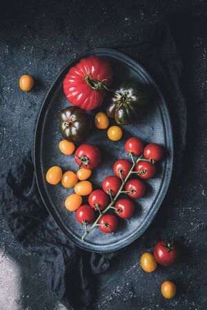 Ripe colorful different tomatoes on plate, top view