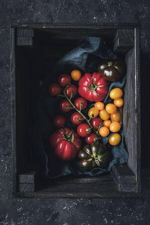 Ripe colorful different tomatoes in wooden box.