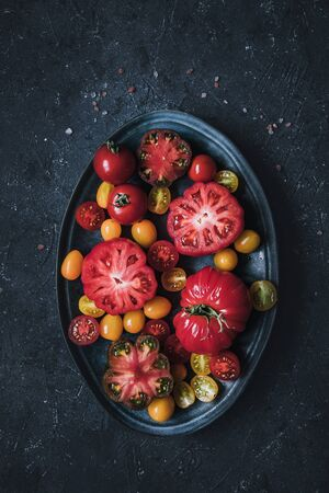 Colourful beautiful tomatoes on plate, view from above