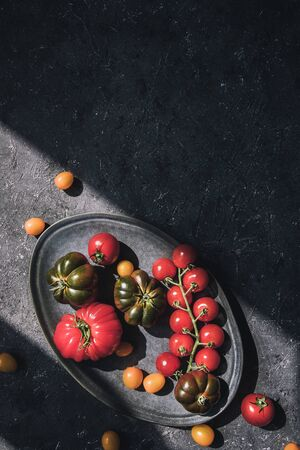 Ripe colorful different tomatoes on plate. Food background with copy space.