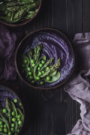 Vegetable spring soup with red cabbage, asparagus and green pea on wooden table, top view. 스톡 콘텐츠