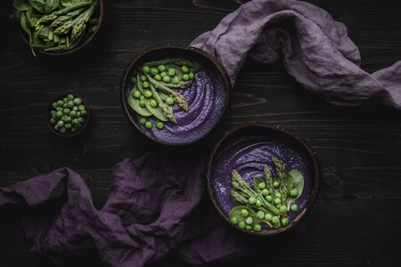Purple vegetable spring soup with red cabbage, asparagus and green pea on wooden table, top view.