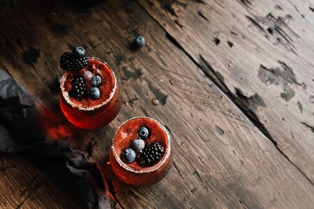 Fresh berry cocktail with blackberries and blueberries on wooden table, with copy space. 스톡 콘텐츠