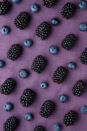 Purple berry background. Fresh juicy blackberries and blueberries on purple background.