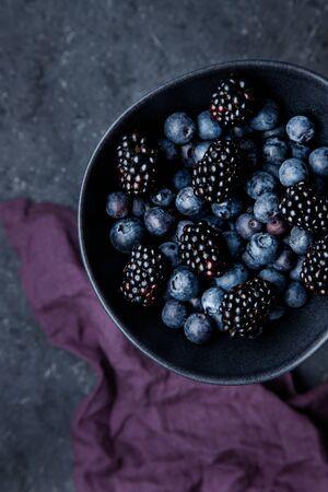Fresh juicy blackberries and blueberries in bowl on table top view