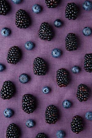 Purple berry pattern. Fresh juicy blackberries and blueberries on purple background.