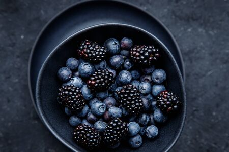 Fresh juicy blackberries and blueberries in bowl on table, close up.