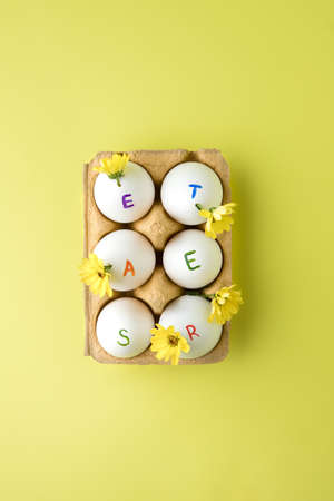 Easter holiday. The word Easter written on eggs with spring yellow flowers on yellow background.