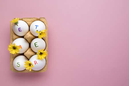 Easter holiday. The word Easter written on eggs with spring yellow flowers on pink background. Copy space.