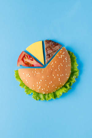Burger pie chart made of burger ingredients on blue background. Creative colorful burger 스톡 콘텐츠