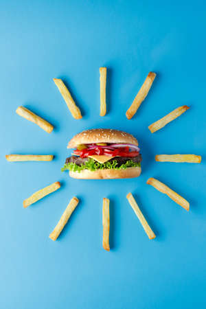 Burger with french fries laid out around on blue backdrop. Creative colorful burger 스톡 콘텐츠