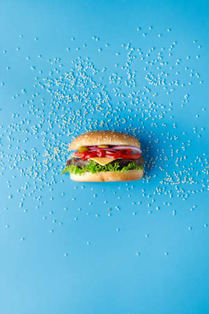 Burger with sesame seeds laid out around on blue backdrop. Creative colorful burger