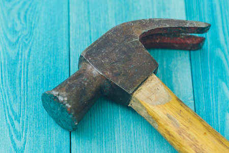 old hammer on a blue wooden background close-up
