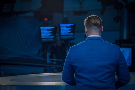 A journalist working on a computer in Newsroom. Back view Stock Photo
