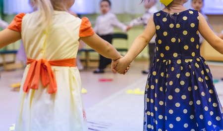 children hold hands in kindergarten close up