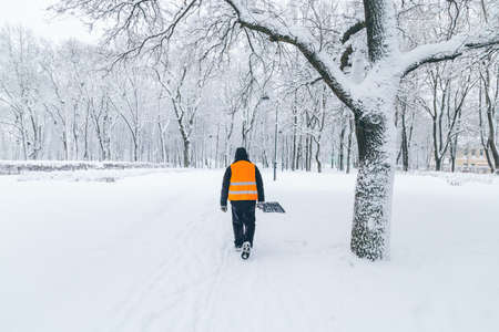 janitor with shovel in the park in winter Standard-Bild