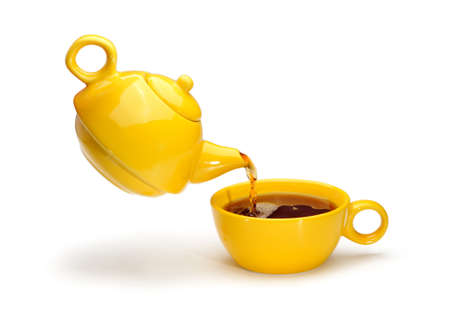Yellow teapot pouring tea into a yellow cup isolated on a white background. photo
