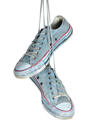 Paar blaue Turnschuhe hängt an den Schnürsenkeln auf einem weißen Hintergrund Lizenzfreie Bilder - 27736023
