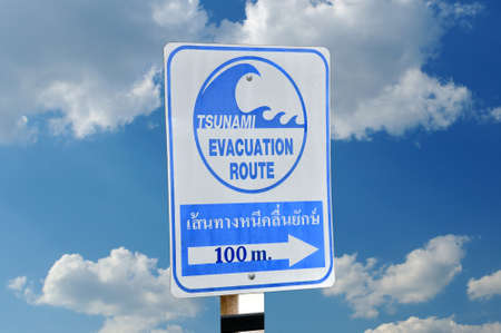 Sign an evacuation route at danger of a tsunami on a blue sky background  photo