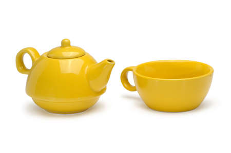 Set of a yellow ceramic teapot and mug isolated on a white background. photo