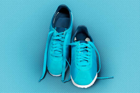 sneakers: Turquoise sneakers on a turquoise sports mat. Top view.