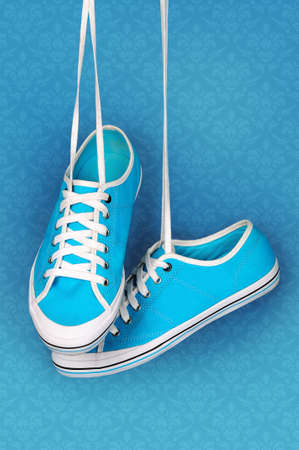 Pair of turquoise sneakers hangs on the laces on a turquoise background.