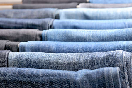 bluejeans: Many colored jeans hanging on hangers.