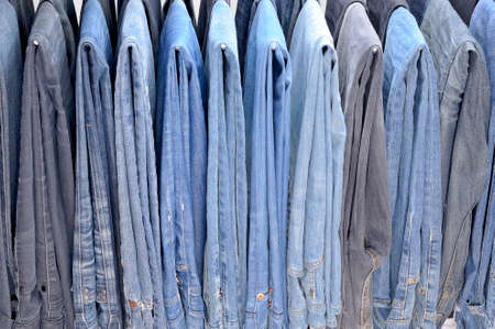 many colored: Many colored jeans hanging on hangers.