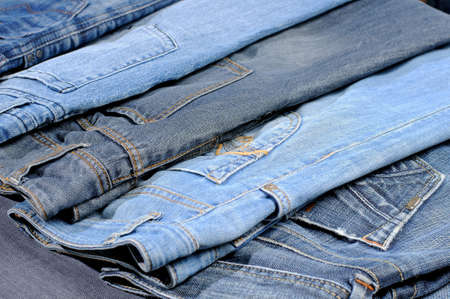 Colored jeans arranged in one row. Stock Photo