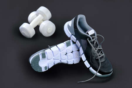 concerning: Black-and-white sneakers stand on heels concerning each other and white dumbbells lie against a dark background