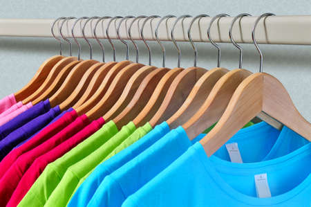Pink, purple, crimson, bright green and turquoise womens T-shirts hanging on wooden hangers on gray background