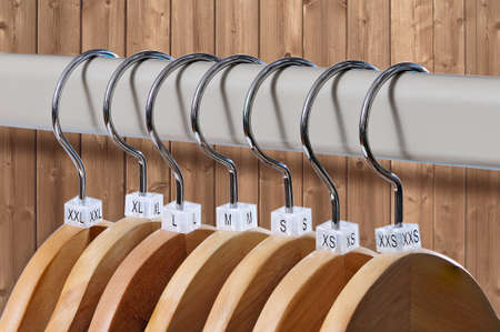s and m: Wooden hangers with plastic indexes of the XXS, XS, S, M, L, XL, XXL sizes on a wooden background Stock Photo