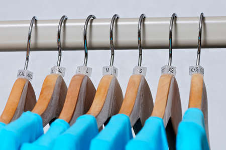 s and m: Turquoise womens t-shirts hang on wooden hangers with indexes of the XXS, XS, S, M, L, XL, XXL sizes on a light background.