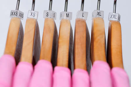 s and m: Pink womens t-shirts hang on wooden hangers with indexes of the XXS, XS, S, M, L, XL, XXL sizes on a light background.