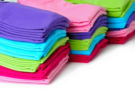 Pink, purple, crimson, bright green and turquoise womens T-shirts lie piles on a white background. Stock Photo
