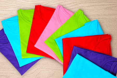Turquoise, light blue, green, red, pink women's t-shirts lie on a wooden background