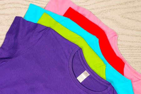 Türkis, hellblau, grün, rot, rosa T-Shirts liegen auf einem hölzernen Hintergrund.