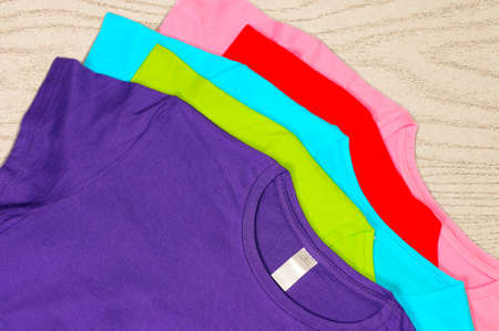 Türkis, hellblau, grün, rot, rosa T-Shirts liegen auf einem hölzernen Hintergrund. Lizenzfreie Bilder - 39363466