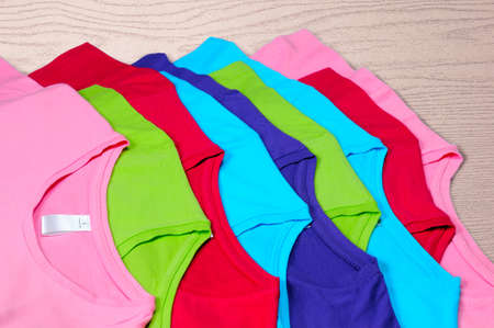 Turquoise, light blue, green, red, pink women's t-shirts lie on a wooden background.