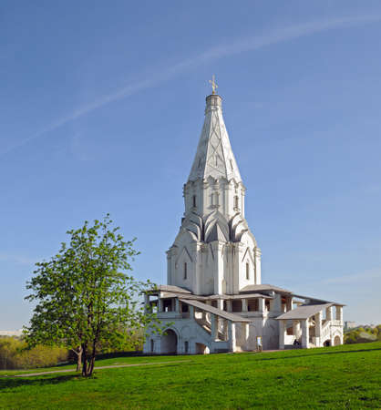 the ascension: Church of the Ascension against the blue sky and a tree in the foreground in Kolomenskoye Moscow