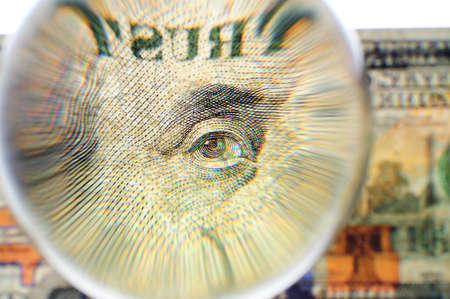 us dollars: Glass sphere on a banknote of 100 US dollars. The increased image of an eye of Benjamin Franklin and the word Trust against a blurred background of 100 US dollars bill.