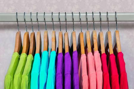 ropa casual: Rosa, púrpura, carmesí, verde y azul turquesa brillante de las mujeres camisetas que cuelgan en perchas de madera sobre fondo claro. Vista lateral. Foto de archivo