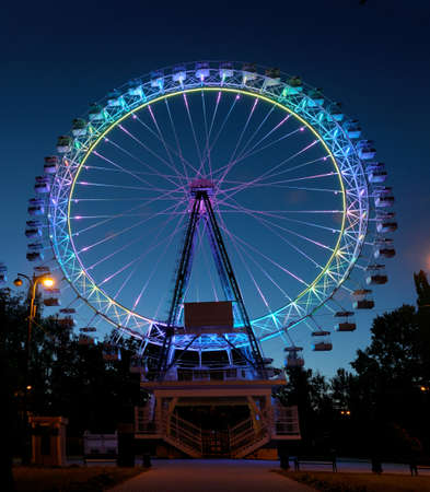 Ferris wheel with multi-colored illumination against the dark blue night sky.
