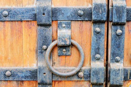 iron gate: Part of the old wooden gates with handle in the form of ring studded with metal plates